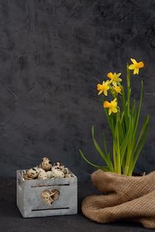 水仙の黄麻布の新鮮な花と木製のバスケットに卵の装飾