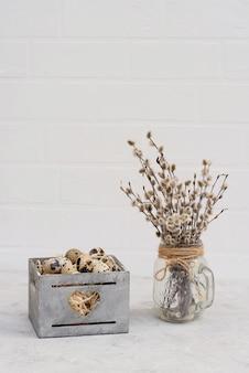な柳の枝が付いている木製のバスケットのウズラの鳥の卵の装飾。