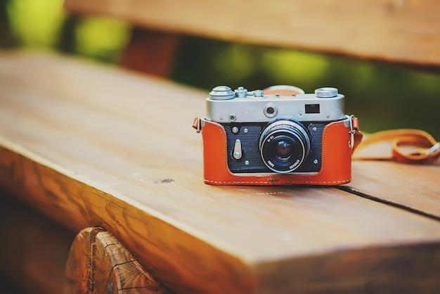 Старая ретро камера на деревянной скамейке в солнечном зеленом лесу