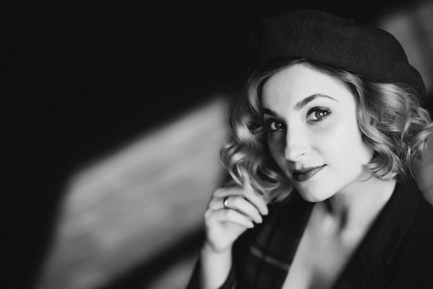ベレー帽の美しいブロンドの女の子は、レトロなスタイルの黒と白のカメラを見てください。