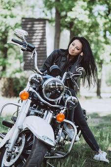 Красивая женщина с длинными волосами в кожаной одежде на открытом воздухе в летний день. байкер женщина.