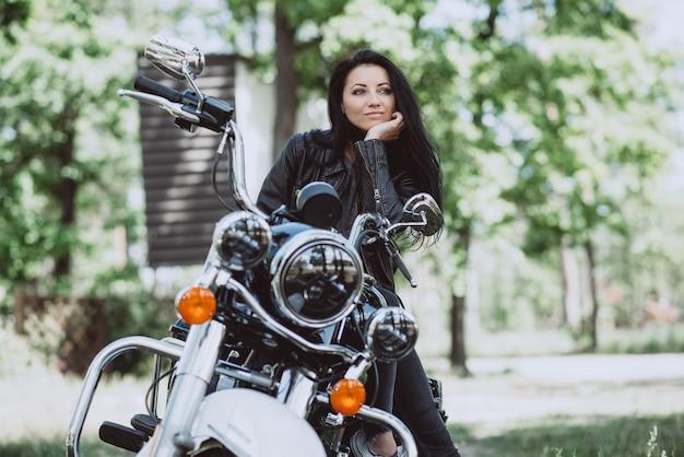 Байкер женщина в кожаной куртке на мотоцикле смотрит вдаль в солнечный летний день