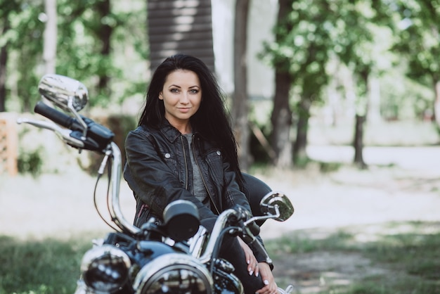 Байкер женщина в кожаной куртке на мотоцикле в солнечный летний день