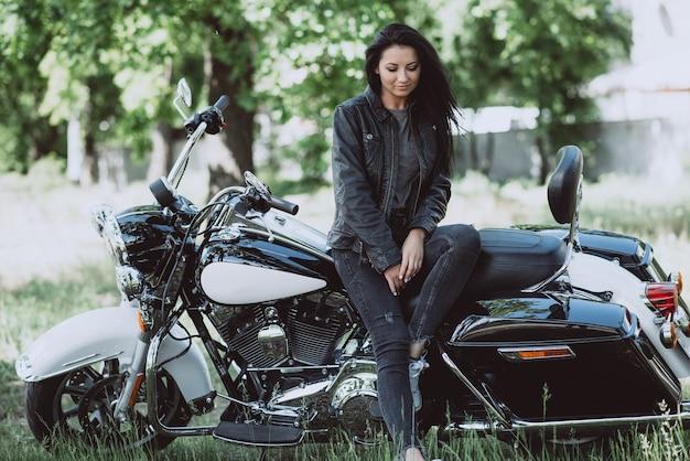 Женщина байкер сидит на своем мотоцикле в солнечный летний день