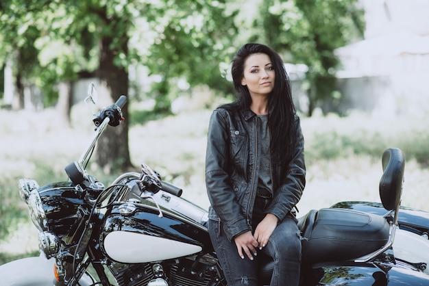 Байкер женщина в кожаной куртке сидит на своем мотоцикле.