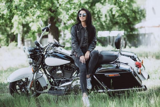 Байкер женщина в кожаной куртке и солнцезащитные очки сидит на своем мотоцикле.