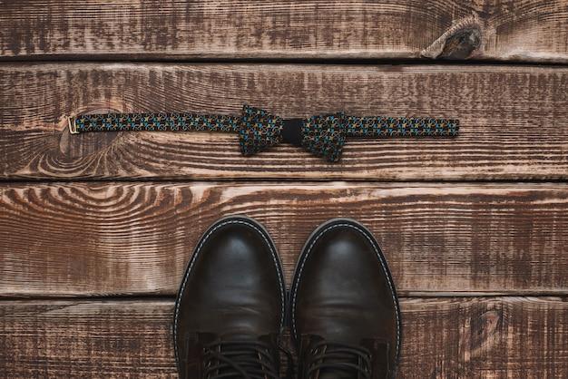 Мужские аксессуары галстук и кожаная обувь на деревянном столе. квартира лежала.