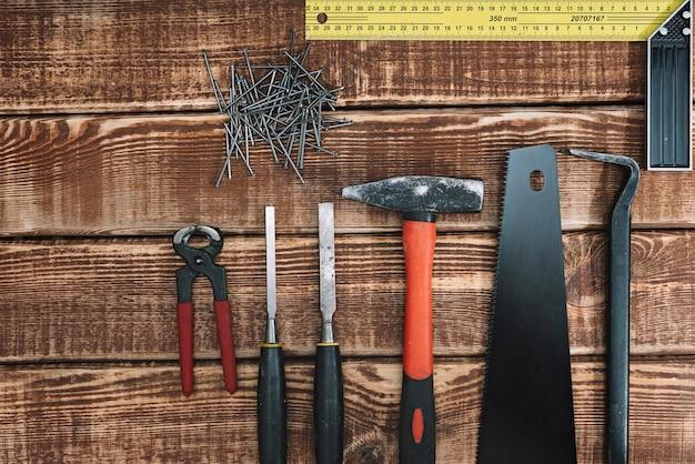 木製のテーブルとコピースペースの木工ツールのコレクション:大工、職人の技、手作りのコンセプト、フラットレイアウト。のこぎり、ハンマー、ノミ、釘、定規。