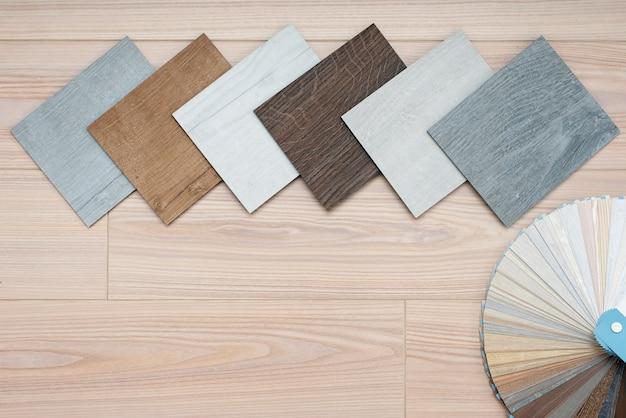 Пример каталога роскошных виниловых напольных плиток и дизайнерской палитры с текстурами с новым дизайном интерьера дома или пола на светлом деревянном столе.