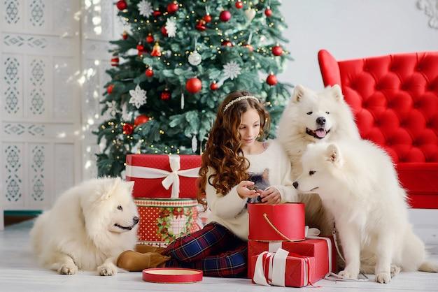 Маленькая красивая девочка и три больших пушистых белых пса рядом с новогодней елкой распаковывают красные коробки с подарками. новогодний праздничный интерьер.