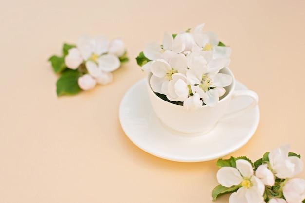 ベージュ色の背景のコーヒーカップに花が咲く白い春のリンゴの木。春夏のコンセプトです。グリーティングカード。