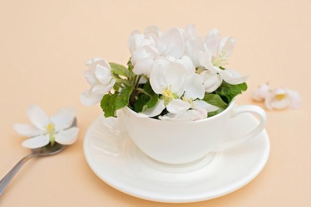 白い春のリンゴの花はベージュ色の背景にスプーンでコーヒーカップに咲く花です。春夏のコンセプトです。グリーティングカード。