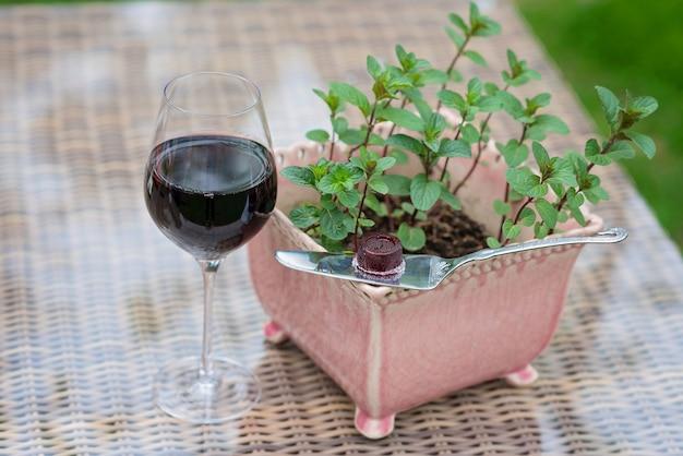 Стакан конфет красного вина и мармелада на столе рядом с мятным горшком.
