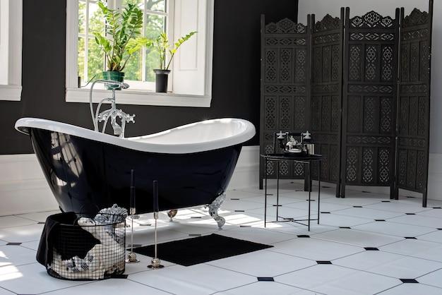 日当たりの良い大きな窓付きの銀の備品を備えた黒と白のモダンなバスルーム。インテリアデザインのコンセプト