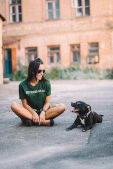 夏の晴れた日に屋外の彼女のペットの犬スタッフォードシャーブルテリアを歩く美しい少女は、道路を座っています。