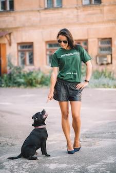 夏の晴れた日に彼女のペットの犬のスタッフォードシャーブルテリアを屋外で歩く美しい少女。動物の訓練。