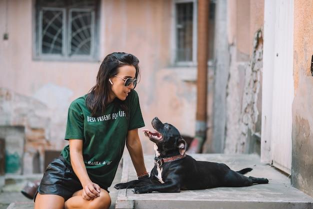 夏の晴れた日に屋外で彼女の犬のスタッフォードシャーブルテリアを歩く美しい少女。彼らは中庭の階段に座っています。