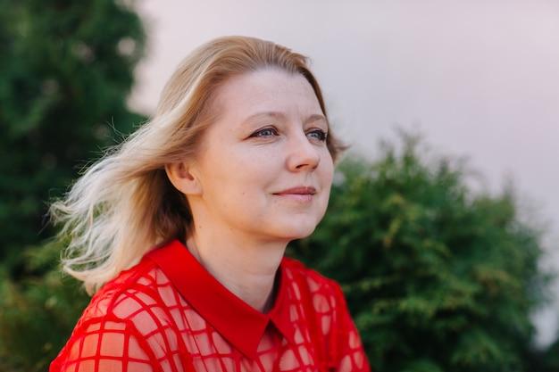 Красивая женщина в красной блузке. морщины на лице женщины. блондинка в красной блузке красивая мама