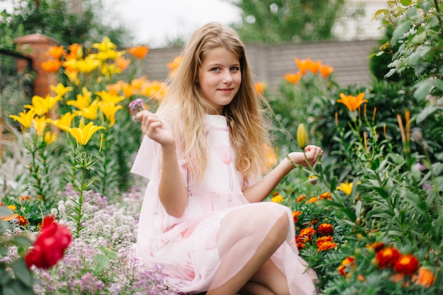 Красивая голубоглазая девушка с длинными светлыми волосами. маленькая девочка в розовом платье фламинго. девушка в цветочном саду. лето яркое, эмоциональное фото. большой, густой, яркий цветник рядом с домом.