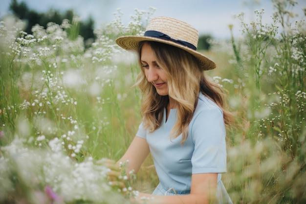 Красивая белокурая девушка в поле ромашек. женщина в голубом платье в поле белых цветов. девушка с букетом ромашек. летнее нежное фото в деревне. полевые цветы. девушка в соломенной шляпе
