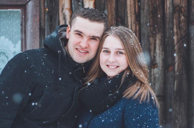 冬のラブストーリー。雪に覆われたクリスマスツリーの近くの夫と妻。お正月気分
