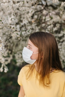 Портрет грустно молодая женщина в защитной медицинской маске с цветами возле цветущего дерева в весеннее время. концепция весенней аллергии