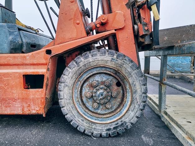 Переднее колесо крупным планом старого автопогрузчика