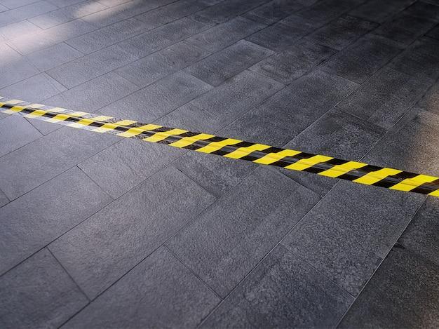 下にある電気ケーブルを覆うタイル張りの床に黄色黒安全警告テープ