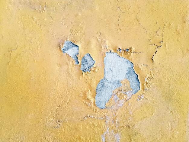 汚れたピールオフ黄色壁テクスチャのフルフレームの背景