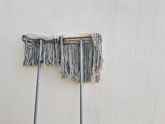 古い汚れた壁に対してハウスキーピングリーンリーン用の中古モップ