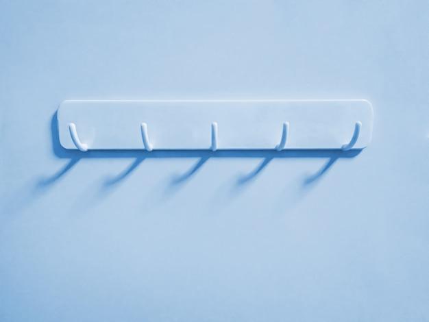 シアンの壁に掛かっている布用のシアンのプラスチック製のフック