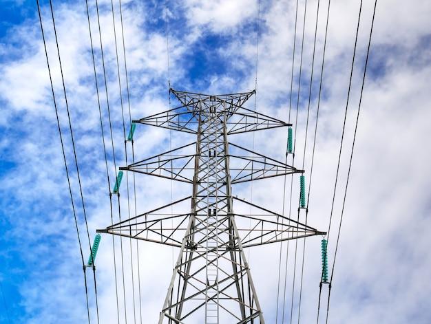 青い曇り空に対する高電圧タワー構造と送電線