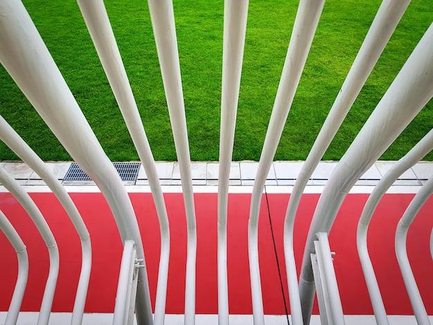 赤い道路と緑の芝生の上の白い曲がった管壁の高角度のビュー