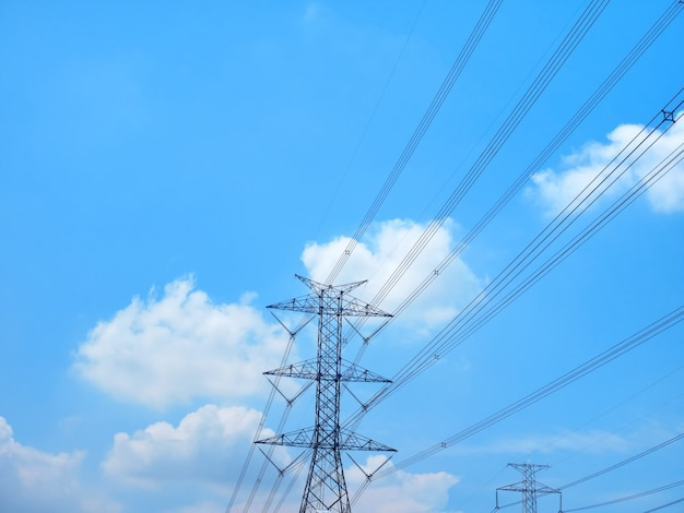 青い曇り空に対する高電圧塔と送電線の低角度のビュー