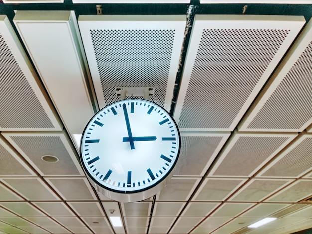 天井からぶら下がっている照明付きアナログ時計
