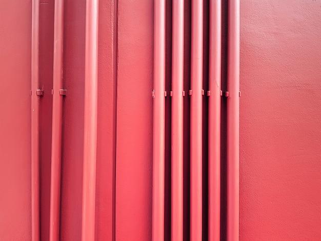Ряды вертикальных красных труб на красной стене