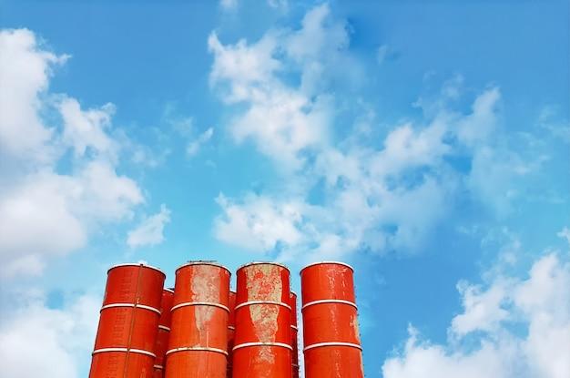 青い曇り空を背景に混合コンクリートタンクの低角度のビュー