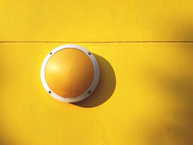 Круглый желтый светильник светильник на ярком фоне желтой стены