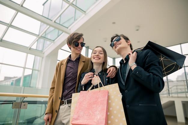 ショッピングモールでのこぎりについて話し合っている紙袋を持った魅力的な買い物中毒者