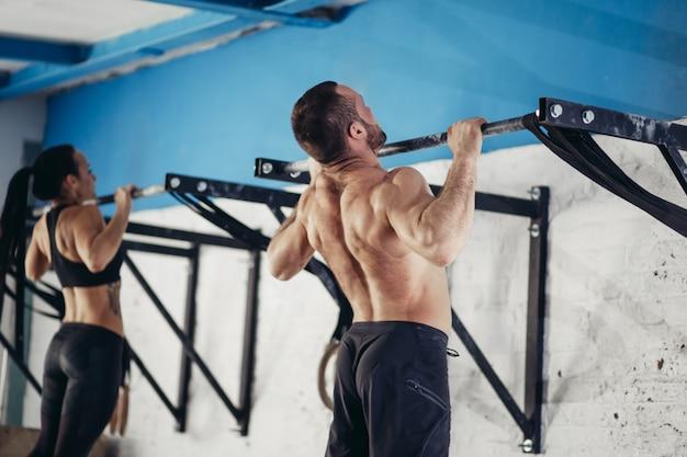 Фитнес красавец делает погружения упражнения с использованием колец в тренажерном зале