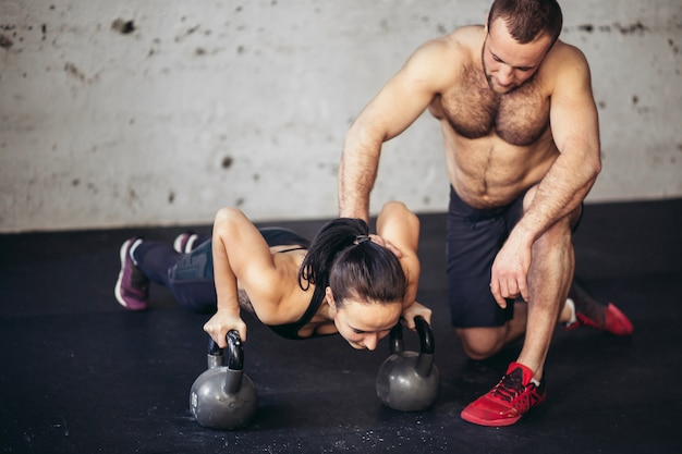 フィットネストレーニングでトレーナーの男性と女性の腕立て伏せ強さ腕立て伏せ
