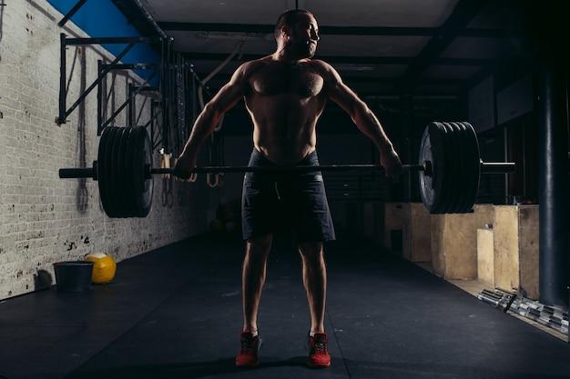 バーベルの演習を行うジムで筋肉男のトレーニング