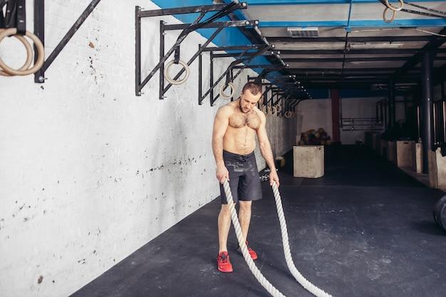 Человек с боевыми канатами в тренажерном зале