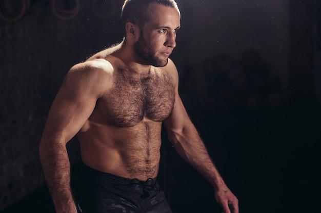 健康クラブでポーズをとって身体にフィットする男