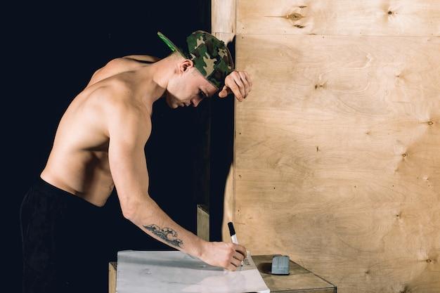 Фитнес спортивный человек, пишущий на пустой блокнот