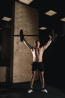 ジムで頭の上にバーベルを上げてひげの電車で残忍な筋肉男