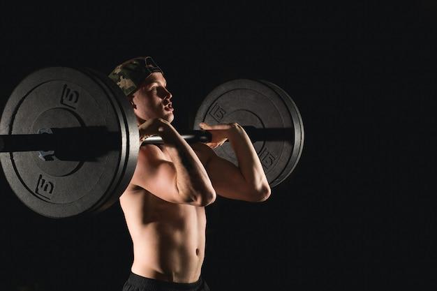 重りを持ち上げる男。バーベルの演習を行うジムで筋肉男のトレーニング