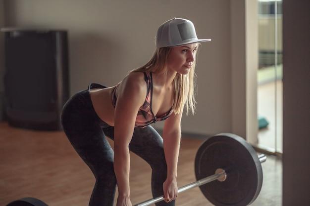 ジムでバーベルでワークアウトフィットの若い女性の完全な長さ。ジムで運動のボディービルダーの女性。