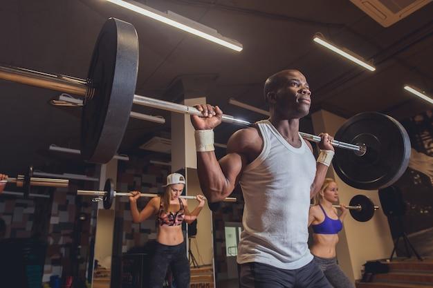 アスリートの友人がジムクラブ内のバーベルでトレーニング。若い人たちは、筋力トレーニングをしています。健康的なライフスタイルとボディービルのコンセプト