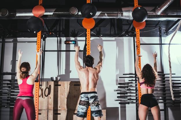 フィット、スポーツ、運動のコンセプト-ジムでメディシンボールトレーニングを持つ人々